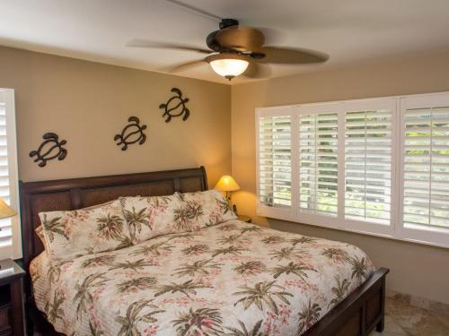 Master Bedroom has a Cal-King bed, ceiling fan, flat screen TV & a partial view.